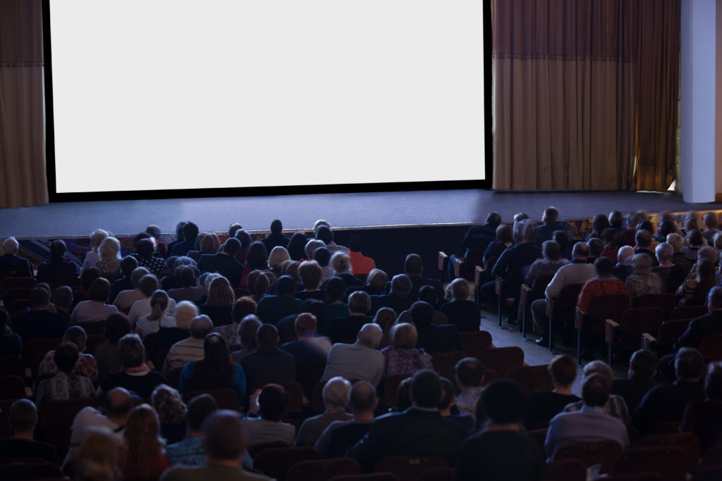 Audience seated in front of an empty stage with a blank white screen in a darkened auditorium, high angle view